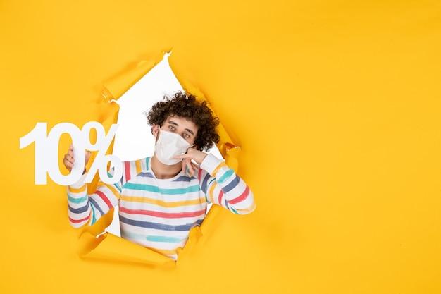 Jovem macho com máscara estéril segurando um texto na foto amarela venda de pandemia de saúde secreta de frente