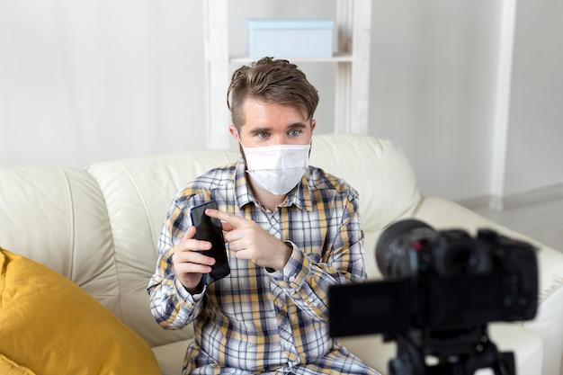 Jovem macho com máscara facial gravando vídeo em casa