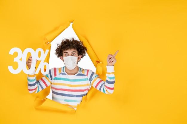 Jovem macho com máscara segurando vírus da cor amarela, saúde covida - foto pandêmica