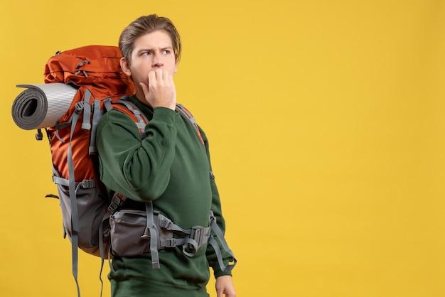 Jovem macho com mochila se preparando para uma caminhada