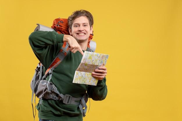 Jovem macho com mochila segurando mapa