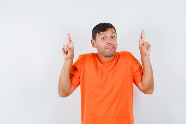 Jovem macho com os dedos cruzados na camiseta laranja e parecendo otimista