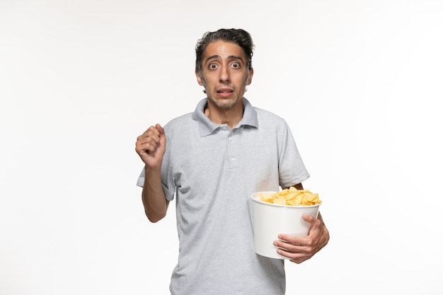 Jovem macho comendo batata frita assistindo filme na mesa branca