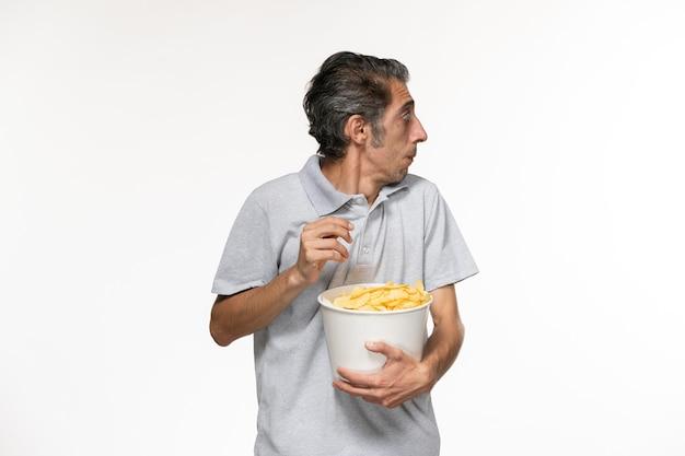 Jovem macho comendo batata frita assistindo filme na superfície branca