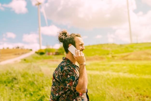 Jovem, macho, conversando, ligado, telefone móvel, em, rural