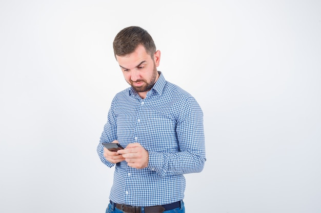 Jovem macho conversando no celular em camiseta, jeans e parecendo hesitante. vista frontal.