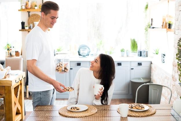Jovem macho dando biscoitos para namorada étnica