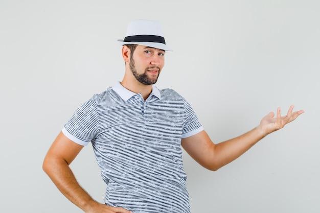 Jovem macho dando boas-vindas ou mostrando algo em t-shirt, chapéu e parecendo confiante. vista frontal.