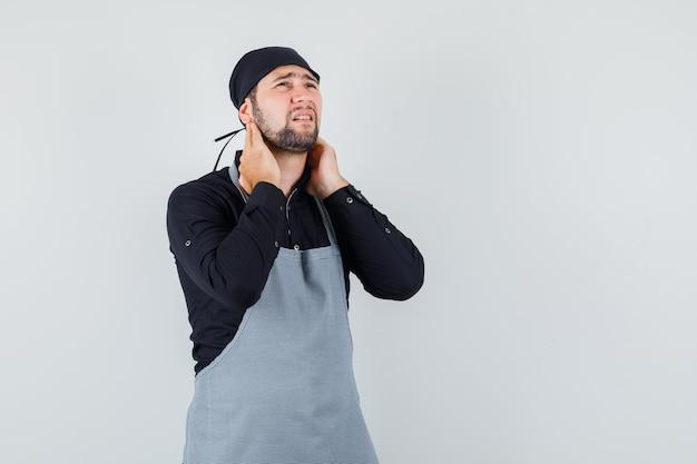 Jovem macho de camisa, avental, sofrendo de dor no pescoço e parecendo cansado, vista frontal.