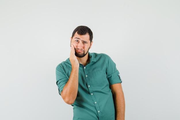 Jovem macho de camisa verde, sofrendo de dor de dente e parecendo dolorido, vista frontal.