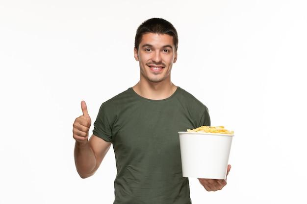 Jovem macho de camiseta verde segurando uma cesta com batata cips no fundo branco filme prazer solitário vista frontal