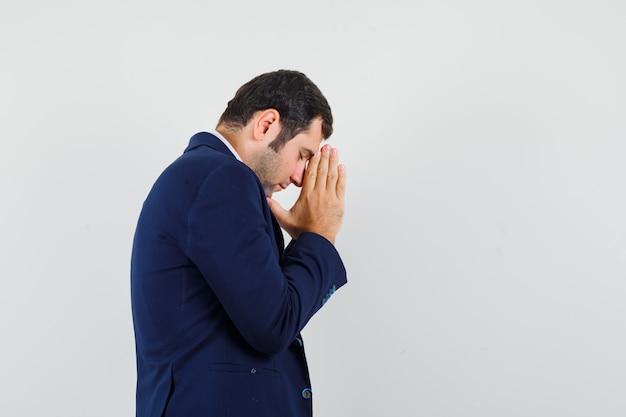 Jovem macho de mãos dadas em gesto de oração na camisa e jaqueta e olhando esperançoso.