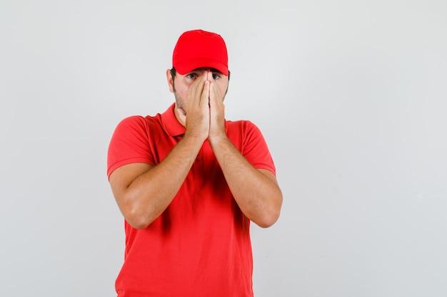 Jovem macho de mãos dadas no rosto em t-shirt vermelha, boné e parecendo assustado.