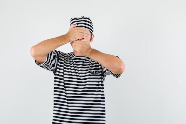 Jovem macho de mãos dadas nos olhos e boca em t-shirt, chapéu e parecendo assustado. vista frontal.