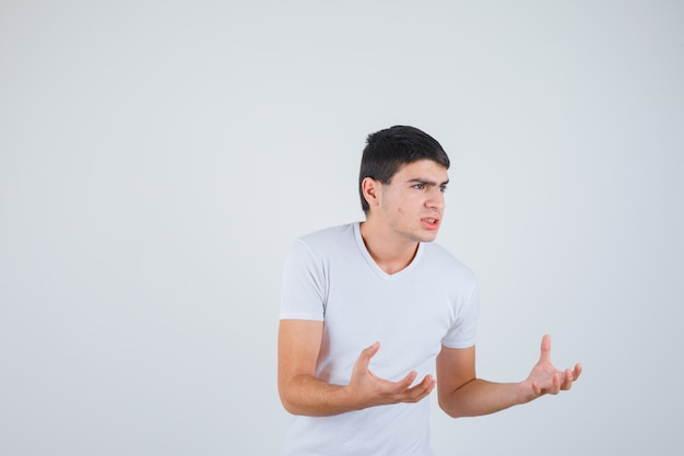 Jovem macho de mãos dadas para pegar algo na t-shirt e olhar sério. vista frontal.