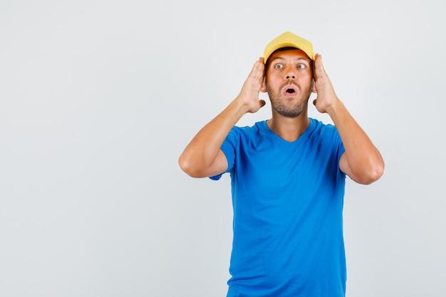 Jovem macho de mãos dadas perto do rosto em uma camiseta azul