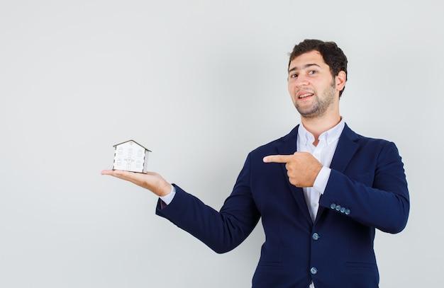 Jovem macho de terno apontando o dedo para o modelo da casa e olhando confiante, vista frontal.