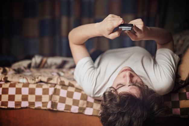 Jovem macho deita-se na cama de cabeça para baixo e conversa em seu gadget de telefone celular.