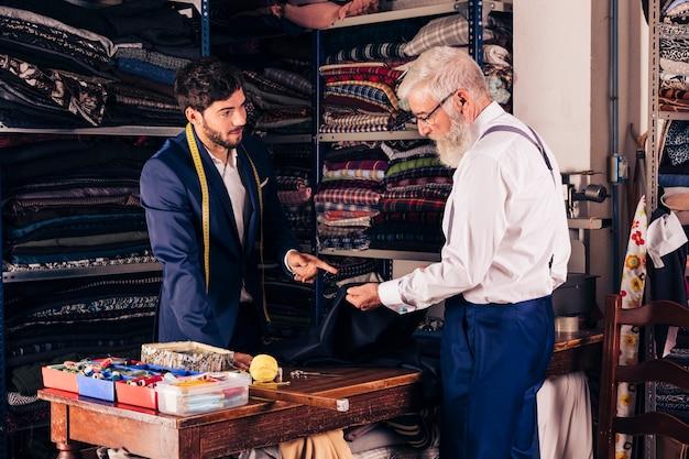 Jovem, macho, desenhista moda, mostrando, azul, tecido, para, seu, cliente, em, a, loja