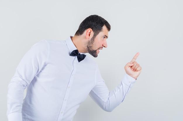 Jovem macho em camisa branca avisando alguém com o dedo e parecendo nervoso, vista frontal.