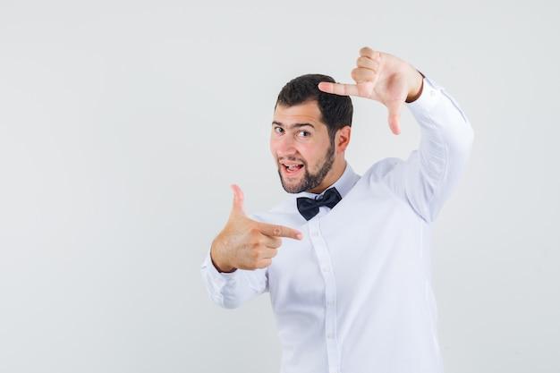 Jovem macho em camisa branca fazendo gesto de quadro e olhando alegre, vista frontal.