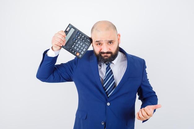 Jovem macho em camisa branca, jaqueta segurando calculadora perto do olho e parecendo confuso, vista frontal.