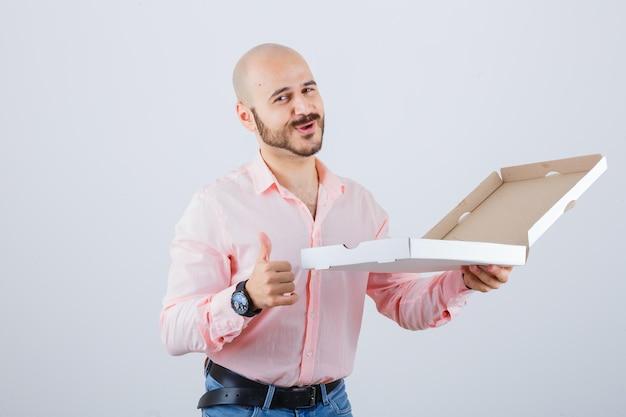 Jovem macho em camisa, jeans aparecendo o polegar e parecendo confiante, vista frontal.