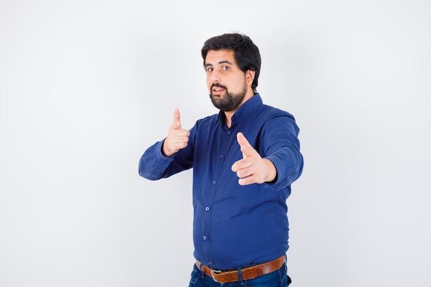 Jovem macho em camisa, jeans, apontando para a frente e olhando confiante, vista frontal.