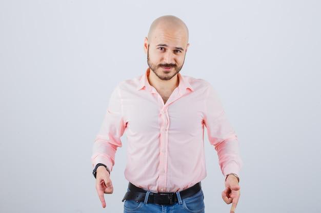 Jovem macho em camisa, jeans apontando para baixo e olhando confiante, vista frontal.