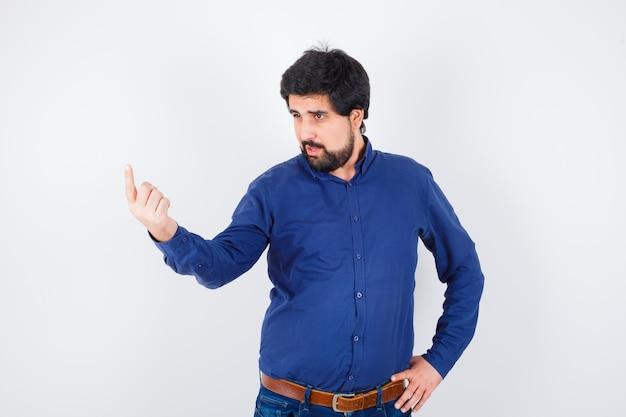Jovem macho em camisa, jeans, apontando para cima e olhando com foco, vista frontal.
