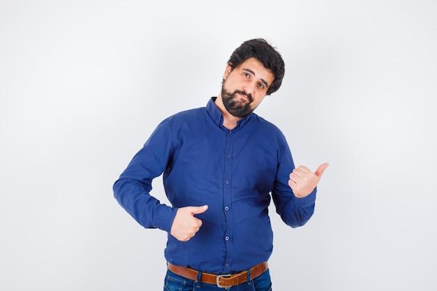 Jovem macho em camisa, jeans, apontando para o canto direito com os polegares e parecendo confiante, vista frontal.