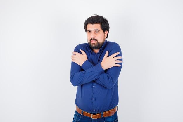 Jovem macho em camisa, jeans esfriando em pé e parecendo desconfortável, vista frontal.