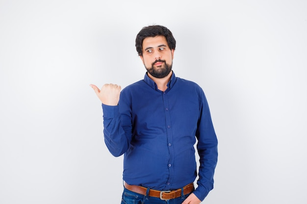 Jovem macho em camisa, jeans, mostrando o polegar do meio e parecendo confiante, vista frontal.
