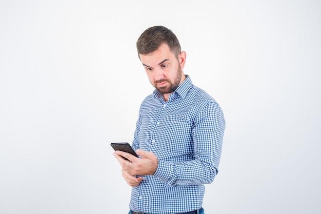 Jovem macho em camisa, jeans, olhando para o celular e parecendo perplexo, vista frontal.
