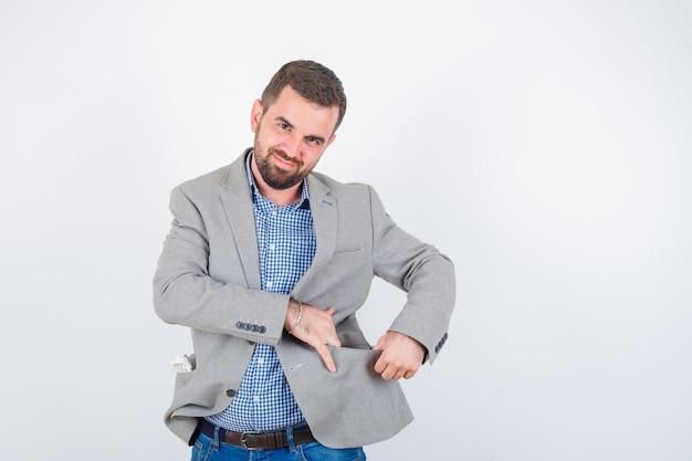 Jovem macho em camisa, jeans, paletó abrindo o bolso da jaqueta com as mãos e olhando alegre, vista frontal.
