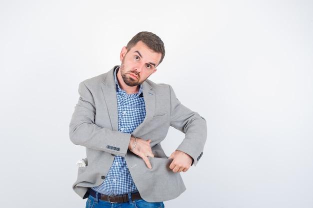 Jovem macho em camisa, jeans, paletó abrindo o bolso da jaqueta com as mãos e olhando sério, vista frontal.