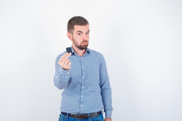 Jovem macho em camisa, jeans segurando mais leve e parecendo confiante, vista frontal.