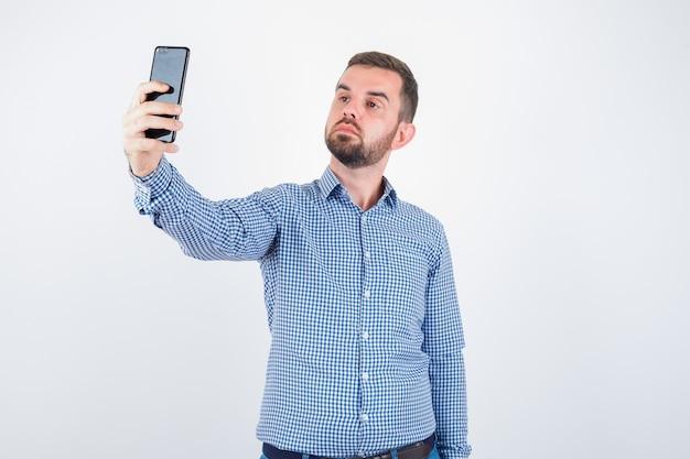 Jovem macho em camisa, jeans, tomando uma selfie e olhando bonito, vista frontal.