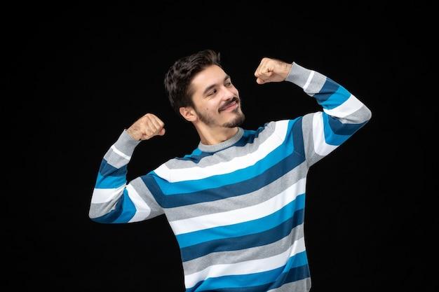 Jovem macho em camisa listrada azul flexionando-se de frente