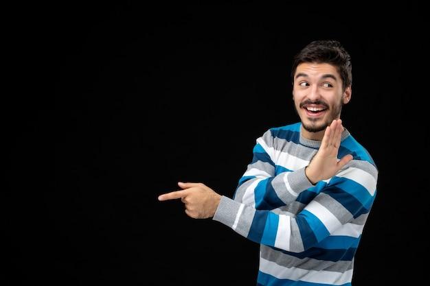 Jovem macho em camisa listrada azul na parede preta modelo de foto em cor humana de frente