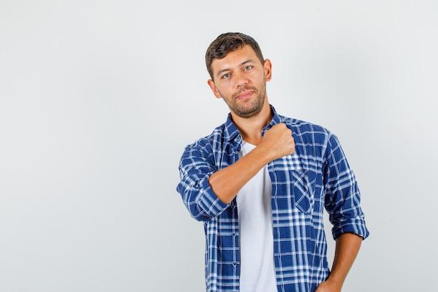 Jovem macho em camisa posando, mostrando o punho cerrado do braço e olhando confiante, vista frontal.