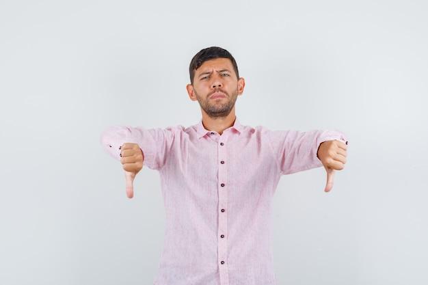 Jovem macho em camisa rosa apontando para baixo e parecendo descontente, vista frontal.
