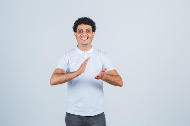 Jovem macho em camiseta branca, calça batendo palmas após grande performance e parecendo alegre, vista frontal.