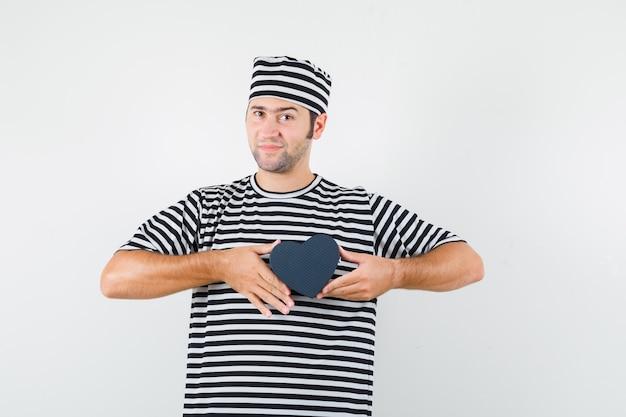 Jovem macho em camiseta listrada, boné segurando mini caixa de presente, vista frontal.
