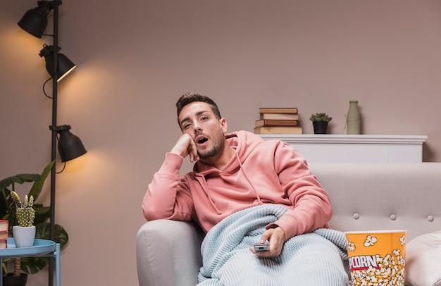Jovem macho em casa assistindo tv