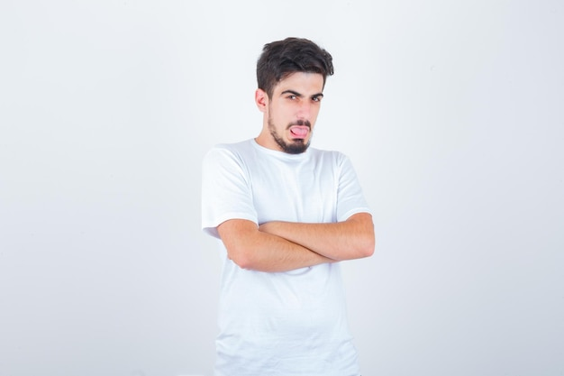 Jovem macho em pé com os braços cruzados, mostrando a língua na camiseta e olhando engraçado, vista frontal.