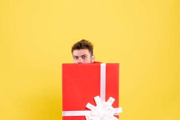 Jovem macho em pé dentro da caixa de presente