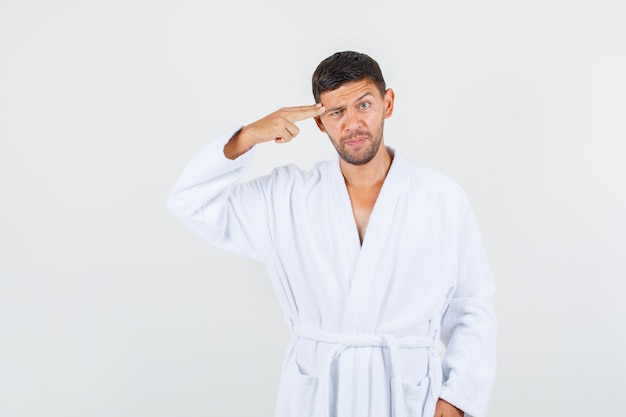 Jovem macho em roupão branco fazendo gesto de suicídio, vista frontal.
