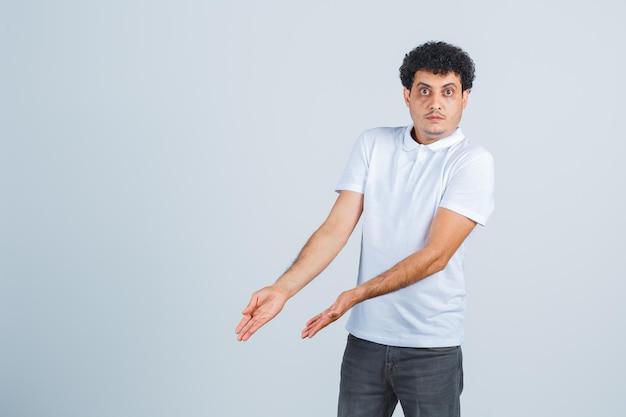 Jovem macho em t-shirt branca, calça mostrando algo abaixo e parecendo confuso, vista frontal.