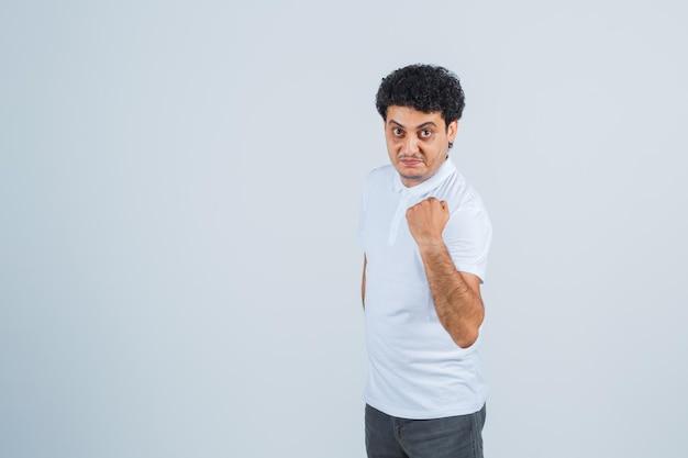 Jovem macho em t-shirt branca, calça mostrando o punho levantado e parecendo confiante, vista frontal.